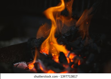 Fire of a barbecue with burning ashes on the air