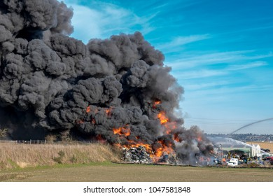 Fire and billowing black smoke in a junkyard of abandoned cars