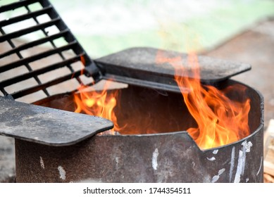 Fire in black metal pit with grate at campsite
