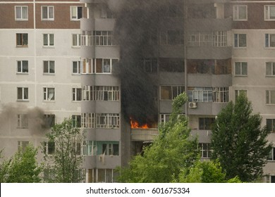 Fire with black smoke in multistory apartment building. Toned