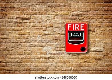 fire break glass alarm switch on the stone wall