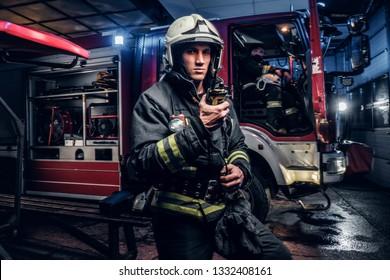 Die Feuerwehr kam in der Nacht an. Feuerwehrmann in einer Schutzuniform, die neben einem Feuerwehrfahrzeug steht und im Radio spricht