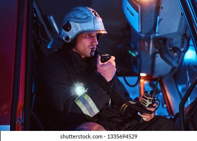 The fire brigade arrived at the night-time. Fireman in a protective uniform sitting in the fire truck and talking on the radio