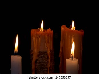 Fire, burning candles on a dark background.