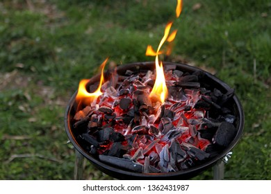 the fire is burning in a compact brazier, the embers smolder