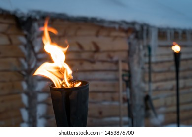 Fire burning inside metal torch in front of a wooden shed in a Sami people village, northern Norway