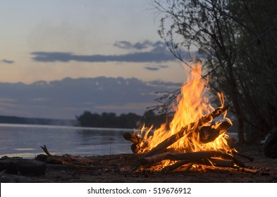 The fire is burning in nature in the evening at sunset on a sandy beach by the river and bushes.