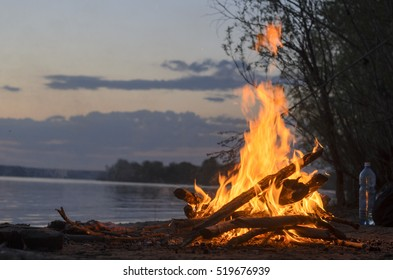 The fire is burning in nature at night on a sandy beach by the river and bushes near the water bottle.