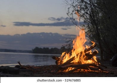 The fire is burning in nature on a sandy beach by the river at sunset tonight.