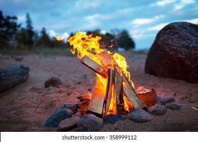 fire burning on the beach at dusk