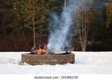 Fire burning in an outdoor firepit in the winter. Smoke rising from a bonfire in a brick fire pit surrounded by snow
