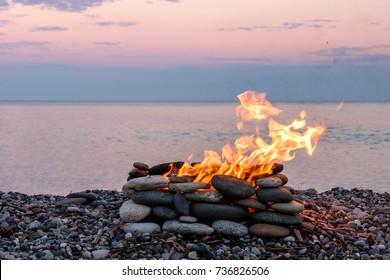 a fire burning in the stone place, beach and sea background