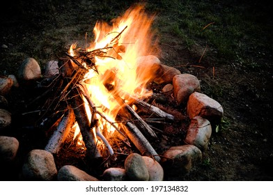 A fire burning in a stone fire ring.