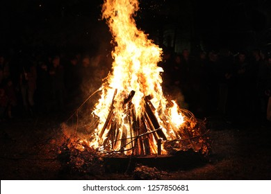 Fire, burning wood. Orthodox Christmas ritual. Fire at the night with unrecognizable people.  Traditional fire ignition in the Balkans.  Orthodox religious ceremony. Badnjak.