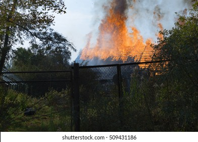 The fire is burning wooden house with an open flame.Living houses fighting a fire. Firefighters extinguished the fire. Fire in a house. Burns house. Burning a residential house fire-fighting