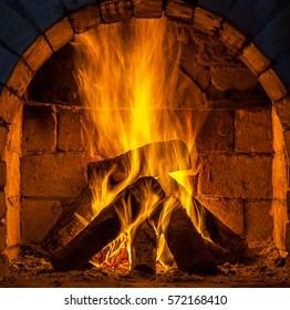 A fire burns in a fireplace.