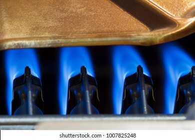 The fire burns in the modern water heater without cover. Closeup, selective focus