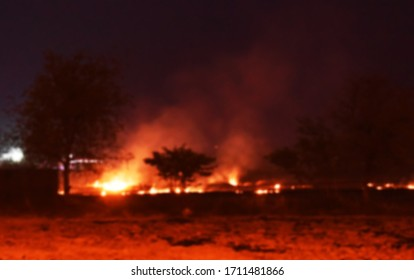 The fire burns rice straw and hay in the field at night. In Northeastern Thailand Southeast Asia  (Blurred images)