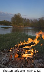 Fire (campfire) against landscape with river background.