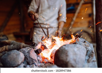 Fire crackling in blacksmith workshop of forging metal. Anonymouse craft smith create objects from wrought iron or steel with helper.