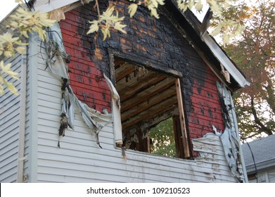 fire damaged home with melted siding and broken glassfire damaged home with melted siding and broken glass