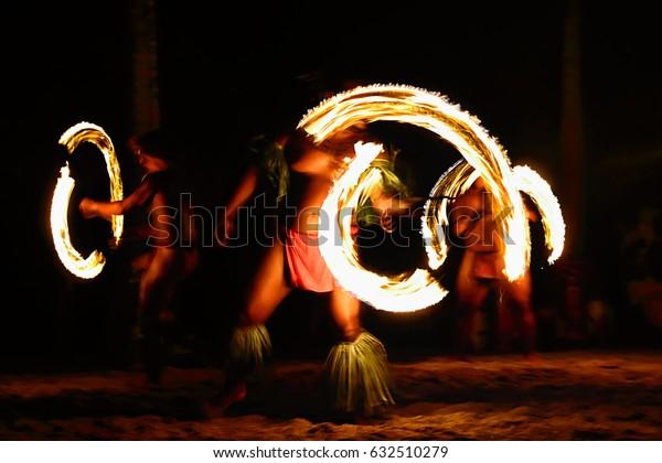 Fire dancers at Hawaii luau show, polynesian hula dance men juggling with fire torches.