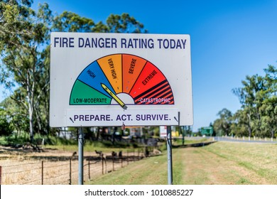 Fire Danger Rating sign on public road in Queensland, Australia. The board indicates daily bushfire threat level and action advice for locals and motorists. Internationally recognised color codes.