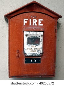 Fire Department fire alarm emergency  call box, red with white letters. Signs read For Fire Open Then Pull Down Hook  worn stained chipped and batter hanging on an old cement apartment building wall
