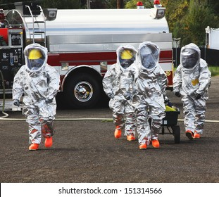 Fire departments & emergency response teams conduct disaster preparedness drills. This HAZMAT team is suited up with PPE to protect them from hazardous materials as they investigate this disaster.