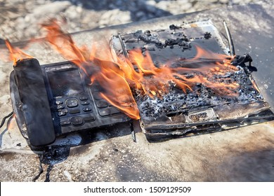 Fire destroys office equipment. Flames burn an office desk with a phone and laptop. Workplace accident.