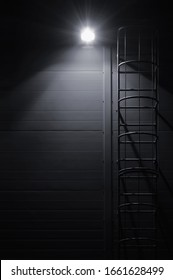 Fire emergency rescue access escape ladder stairway roof maintenance stairs night lantern lamp light shadows industrial building wall vertical closeup copy space background, dark grey black