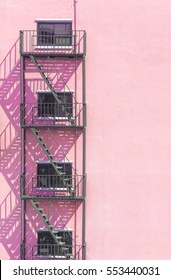 Fire escape metal on light pink Vintage stone wall outside building and shadow staircase pattern.