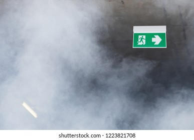 fire escape sign on ceiling with white smoke.