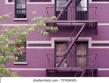 Fire escape stairs mounted to the outside of New York building with purple bricks