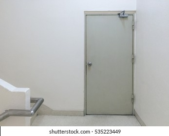 Fire exit door and stairs in empty white office building
