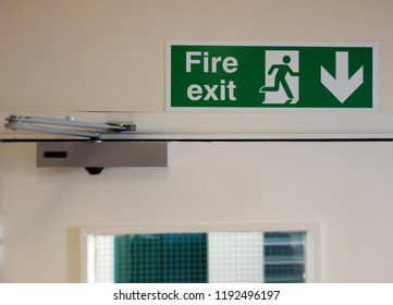 Fire exit sign above the door. Selective focus on green fire exit sign at corner of frame. Space to add text on blurry surrounding background, overhead door closer, door & glass panel. Safety concept.