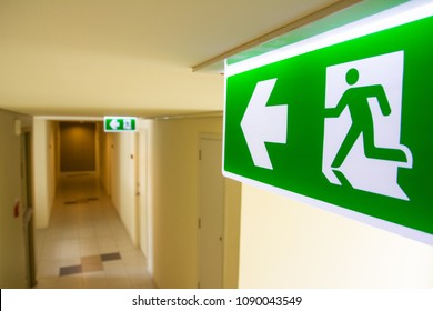 Fire exit sign at  the corridor in building