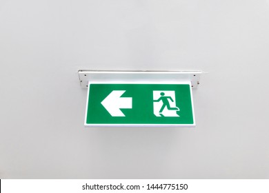 Fire exit sign. Emergency fire exit door exit door on ceiling. Green emergency exit sign showing the way to escape.