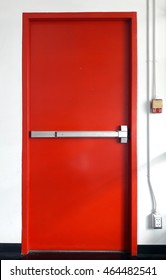 Fire exit steel door red color for evacuation in case of fire, with fire alarm pull switch on the wall near the door
