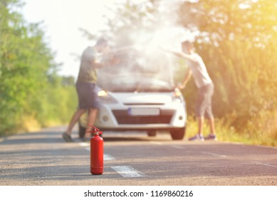 Fire extinguisher against car incident on the road with smoke on the engine