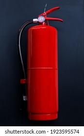 Fire extinguisher on dark background.