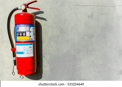 Fire extinguisher on the white wall.