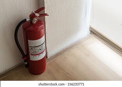 Fire extinguisher on wood floor in corner room