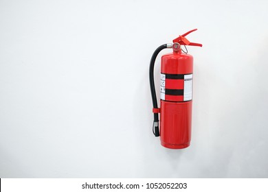 Fire Extinguisher in red cabinet on white wall background.