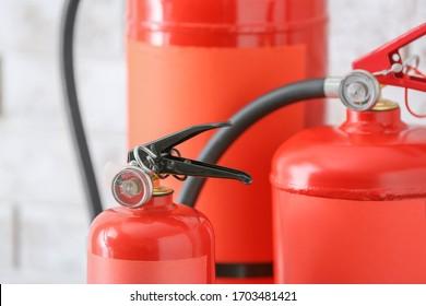 Fire extinguishers near light wall, closeup