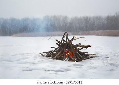 Fire in falling snow on frozen lake