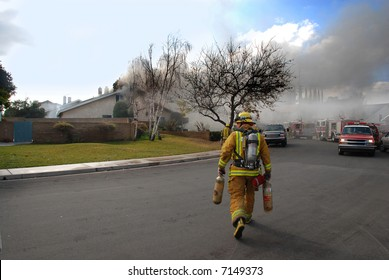 Fire fighter carrying air tanks heads to a house on fire with fire fighters on the roof.