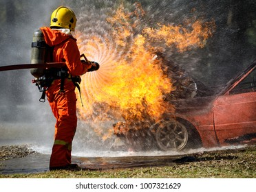 Fire fighter hosing water to  extinguish a fire over the car in accident on the road