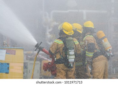 Fire fighters are controlling a fire monitor in order to combat fire. Visible water mist in the background.