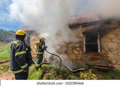 fire fighters subdueing a burning house